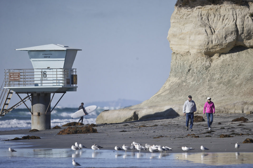 Photo - A couple walks along the beach as a surfer leaves the water on a sunny but cold day Wednesday, Dec. 16, 2015, in Cardiff, Calif.  (AP Photo/Lenny Ignelzi)