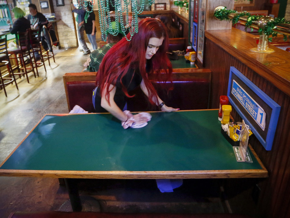 Photo - Michelle Ridgway sanitizes a booth after customers left O'Connell's Irish Pub and Grille on St. Patricks Day in Norman, Okla., Tuesday, March 17, 2020. O'Connell's was following the restrictions at the time to have no more than 50 people gathered together and limited the number of customers allowed in at once. [Nate Billings/The Oklahoman]