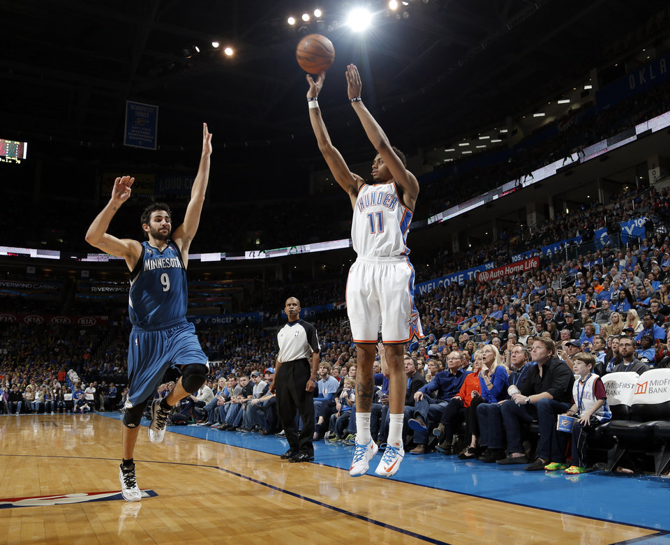 Photo - Oklahoma City's Jeremy Lamb (11) attempts a three-point basket as Minnesota's Ricky Rubio (9) during the NBA game between the Oklahoma City Thunder and the Minnesota Timberwolves at the Chesapeake Energy Arena, Sunday, Dec. 1, 2013. Photo by Sarah Phipps, The Oklahoman