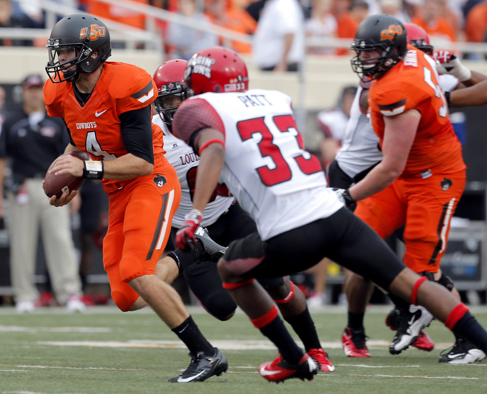 Photo - Oklahoma State's J.W. Walsh (4)  scrambles as Louisiana-Lafayette's Trevence Patt (33) chases him down  during a college football game between Oklahoma State University (OSU) and the University of Louisiana-Lafayette (ULL) at Boone Pickens Stadium in Stillwater, Okla., Saturday, Sept. 15, 2012. Photo by Sarah Phipps, The Oklahoman