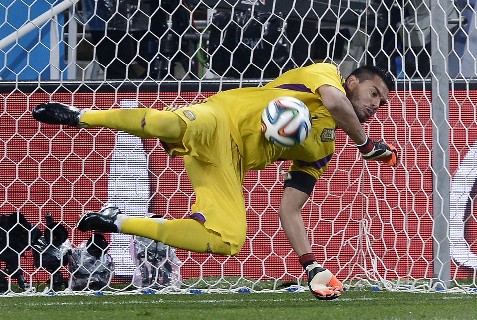 Photo - Argentina's goalkeeper Sergio Romero saves a penalty from Netherlands' Ron Vlaar during a shootout at the end of the World Cup semifinal soccer match between the Netherlands and Argentina at the Itaquerao Stadium in Sao Paulo Brazil, Wednesday, July 9, 2014.  (AP Photo/Manu Fernandez)