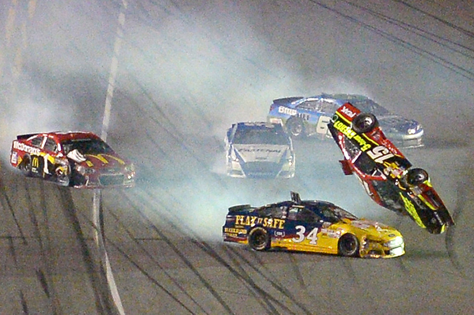 Photo - Clint Bowyer (15) flips over David Ragan (34) after a collision coming out of Turn 4 during the second of two NASCAR Sprint Cup qualifying auto races at Daytona International Speedway in Daytona Beach, Fla., Thursday, Feb. 20, 2014. (AP Photo/Phelan M. Ebenhack)