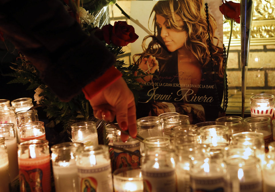 A woman adjusts a flower in front of candles and pictures displayed in tribute to singer Jenni Rivera at the Plaza Mexico shopping center in Lynwood, Calif., early Monday, Dec. 10, 2012. Authorities have not confirmed her death, but Rivera�s relatives in the U.S. say they have few doubts that she was on the Learjet 25 that disintegrated on impact Sunday in rugged territory in Nuevo Leon state in northern Mexico. (AP Photo/Patrick T. Fallon)