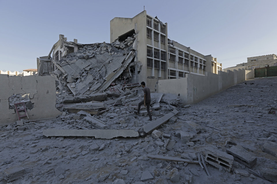 Photo - Palestinian youth inspect the damage of Ali Ibn Abi Talib government school after it was hit overnight in an Israeli strike in Gaza City, in the northern Gaza Strip, Tuesday, Aug. 26, 2014. (AP Photo/Adel Hana)