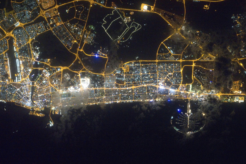 FILE- In this Feb. 22, 2012 file photo, the city lights of Dubai, United Arab Emirates are featured in this image provided by NASA and photographed by an Expedition 30 crew member on the International Space Station. It suddenly seems like Dubai is rediscovering its old habits. That means breathless hype is now back in vogue. Construction plans are again peppered with superlatives. (AP Photo/NASA, File)