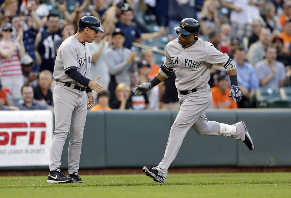 Photo - New York Yankees' Robinson Cano, right, high-fives third base coach Rob Thomson as he rounds the bases after hitting a solo home run in the first inning of a baseball game against the Baltimore Orioles in Baltimore, Monday, May 20, 2013. (AP Photo/Patrick Semansky)
