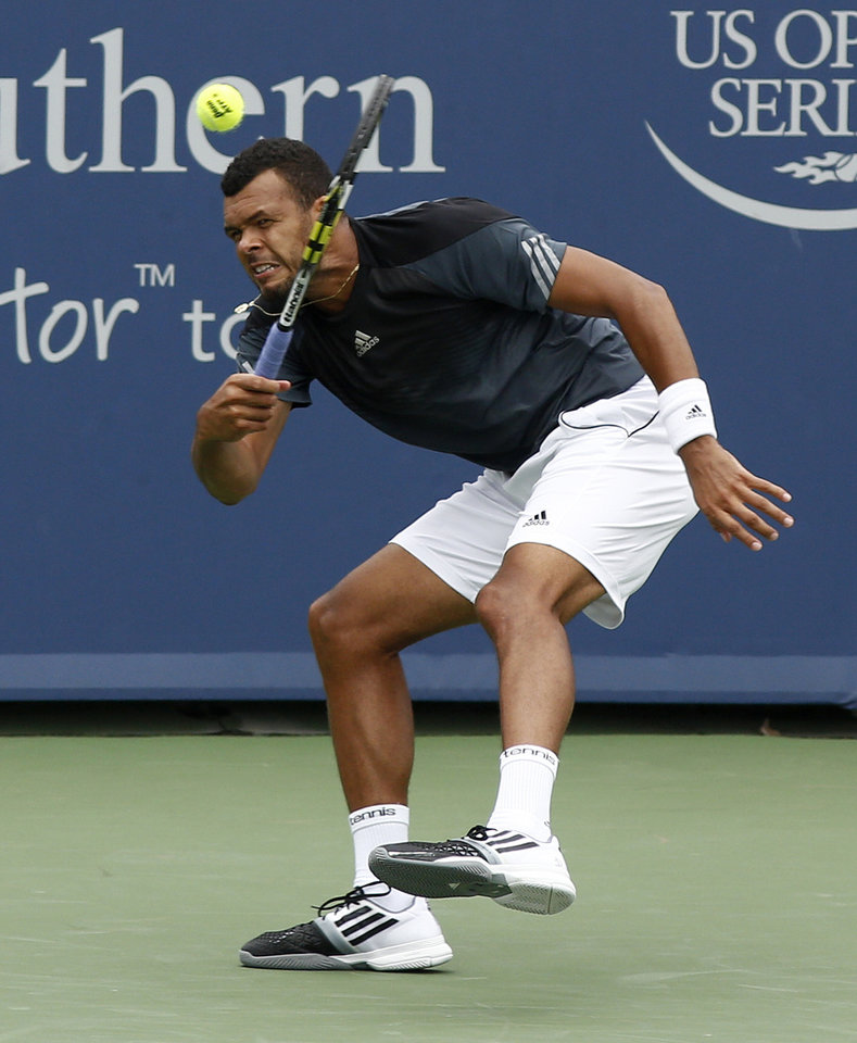 Photo - Jo-Wilfried Tsonga, from France, returns a volley to Mikhail Youzhny, from Russia, during a first round match at the Western & Southern Open tennis tournament, Tuesday, Aug. 12, 2014, in Mason, Ohio. (AP Photo/David Kohl)