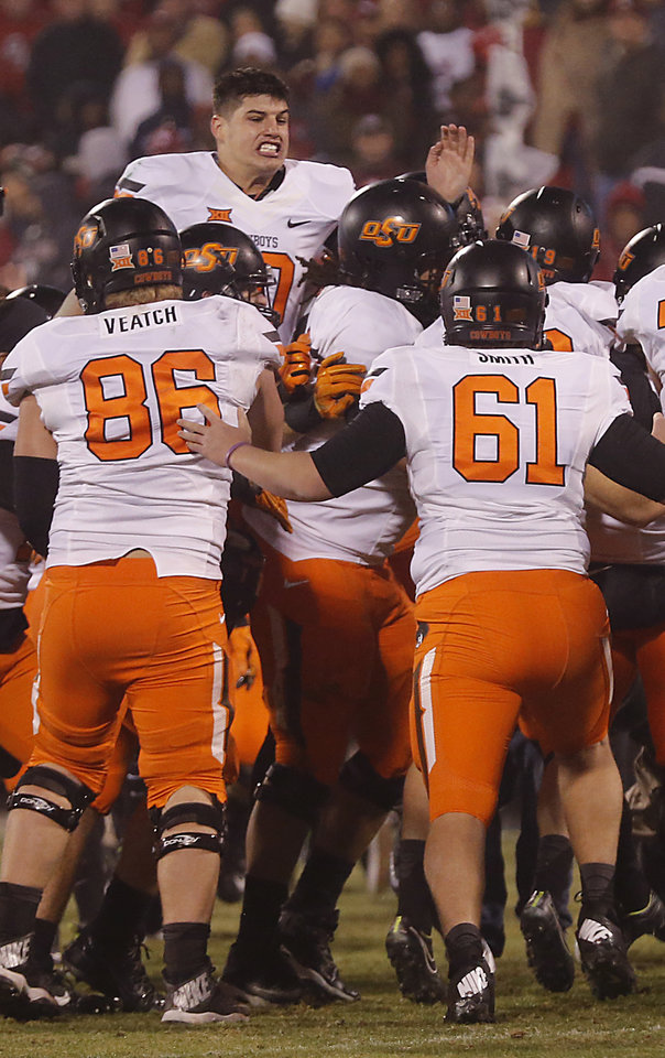 Photo - Oklahoma State's Mason Rudolph (10) celebrates with teammates after the 38-35 overtime win over Oklahoma during a Bedlam college football game between the University of Oklahoma Sooners (OU) and the Oklahoma State University Cowboys (OSU) at the Gaylord Family Oklahoma Memorial Stadium in Norman, Okla. on Saturday, Dec. 6, 2014. Photo by Chris Landsberger, The Oklahoman