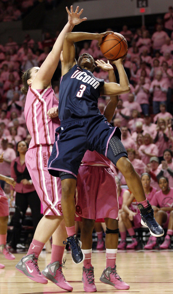 Connecticut guard Tiffany Hayes (3) is fouled by Oklahoma center Jelena Cerina, left, as she shoots in the first half of an NCAA college basketball game in Norman, Okla., Monday, Feb. 13, 2012. (AP Photo/Sue Ogrocki)