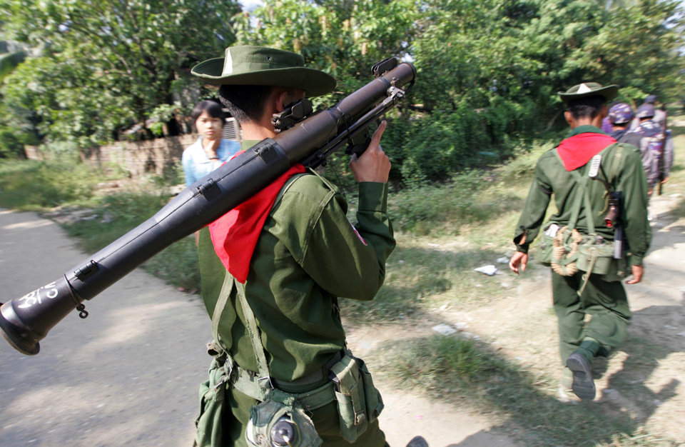 In this photo taken on Nov. 11, 2012, Myanmar soldiers and police walk as they provide security in Sittwe, Rakhine State, western Myanmar. Ethnic Kachin rebels in Myanmar say clashes in the country�s north are continuing despite a government promise to cease fire. An official with the Kachin Independence Army says government forces stopped attacks Saturday, Jan. 19, 2013 around an army base at Lajayang, just south of the rebel-held town of Laiza. But the official says army assaults are under way elsewhere on least three other rebel positions in the region.  (AP Photo/Khin Maung Win)