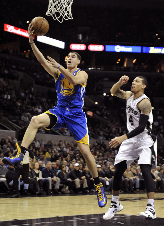 Golden State Warriors guard Klay Thompson, left, scores in front of San Antonio Spurs guard Danny Green, right, during the first half of an NBA basketball game on Friday, Jan. 18, 2013, in San Antonio. (AP Photo/Bahram Mark Sobhani)