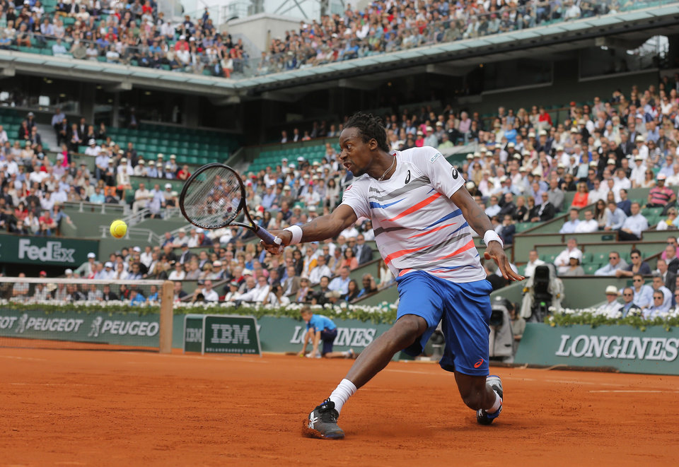 Photo - France's Gael Monfils returns the ball to Spain's Guillermo Garcia-Lopez during their fourth round match of  the French Open tennis tournament at the Roland Garros stadium, in Paris, France, Monday, June 2, 2014. (AP Photo/Michel Spingler)