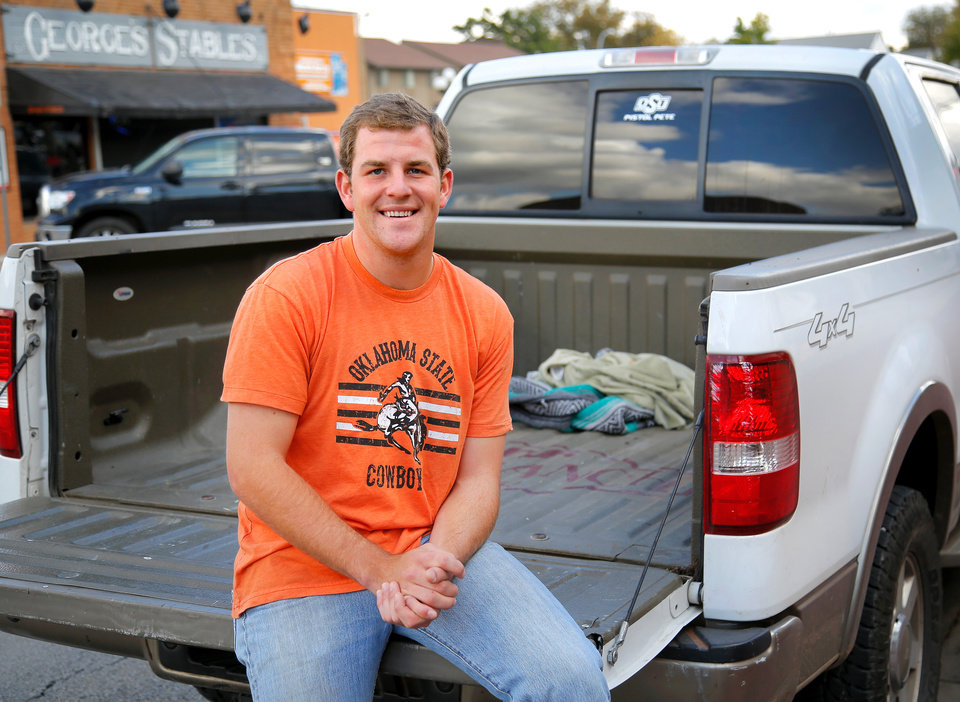 Photo - Taylor Collins is a senior at Oklahoma State University. He also is the OSU mascot, Pistol Pete. Collins participated in last weekend's homecoming parade but had already completed his duties when a woman drove her car into a crowd along the parade route, killing four people and injuring several dozen more.  Collins was nearby when the crash happened and he was flagged down by first responders because they needed to use his truck to transport injured to the hospital. One of those who Collins put in the back seat of his truck is Alleyn Campbell, a 12 year-old boy who suffered a broken leg, and just happens to be a huge fan of Pistol Pete. Collins is shown with the truck he used to take the boy and another victim to the Stillwater hospital. He is photographed in Stillwater on Tuesday, Oct. 27, 2015.  Photo by Jim Beckel, The Oklahoman.