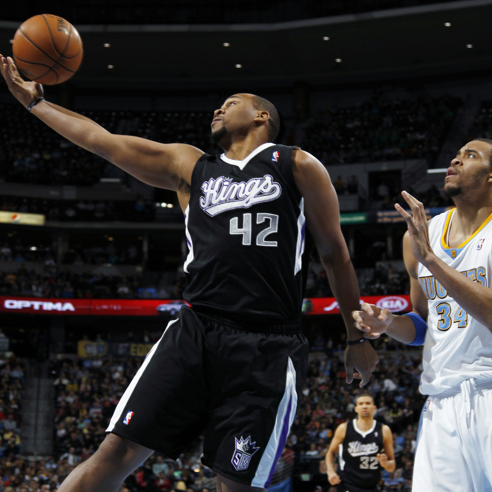 Sacramento Kings forward Chuck Hayes, left, pulls in a rebound in front of Denver Nuggets forward JaVale McGee in the first quarter of an NBA basketball game in Denver on Saturday, Jan. 26, 2013. (AP Photo/David Zalubowski)