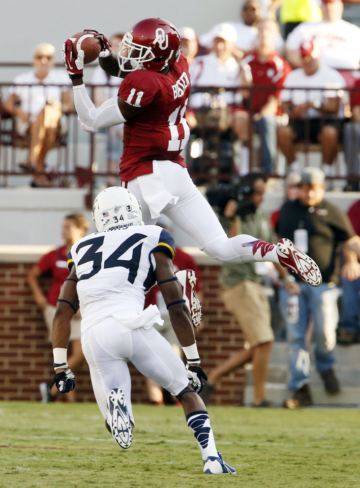 Photo - Oklahoma's Lacoltan Bester (11) catches a pass over Ishmael Banks (34) during a college football game between the University of Oklahoma Sooners (OU) and the West Virginia University Mountaineers at Gaylord Family-Oklahoma Memorial Stadium in Norman, Okla., on Saturday, Sept. 7, 2013. Photo by Steve Sisney, The Oklahoman