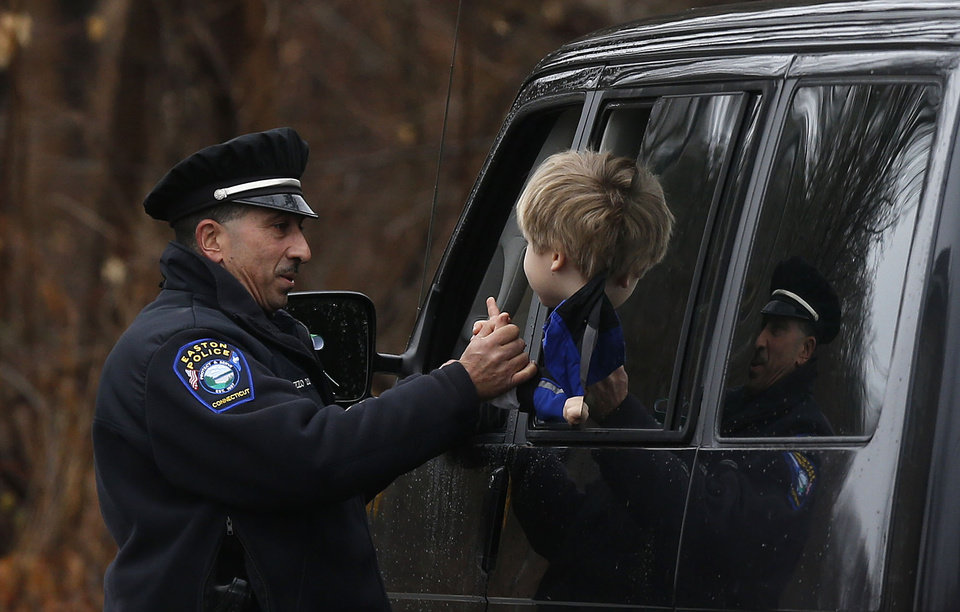 Photo - Easton police officer J. Sollazzo clasps hands with a young student returning to Hawley School, Tuesday, Dec. 18, 2012, in Newtown, Conn.  Classes resume Tuesday for Newtown schools except those at Sandy Hook. Buses ferrying students to schools were festooned with large green and white ribbons on the front grills, the colors of Sandy Hook. At Newtown High School, students in sweatshirts and jackets, many wearing headphones, betrayed mixed emotions.  Adam Lanza walked into Sandy Hook Elementary School in Newtown,  Friday and opened fire, killing 26 people, including 20 children, before killing himself.(AP Photo/Jason DeCrow)