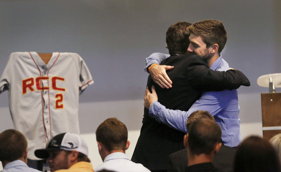 Photo - Jordan Corn, left, hugs Sam Moon before a memorial service for 22-year-old Australian collegiate baseball player Christopher Lane on Saturday, Aug. 24, 2013 in Oklahoma City. Lane was shot in the back and killed last week as he was jogging in an affluent neighborhood in Duncan, in south-central Oklahoma. Corn and Moon played baseball with Lane when they attended Redlands Community College in El Reno, Okla. A jersey bearing the number Lane wore while while he played there is at left. (AP Photo/The Oklahoman, Jim Beckel) LOCAL STATIONS OUT (KFOR, KOCO, KWTV, KOKH, KAUT OUT); LOCAL WEBSITES OUT; LOCAL PRINT OUT (EDMOND SUN OUT, OKLAHOMA GAZETTE OUT) TABLOIDS OUT ORG XMIT: OKOKL102