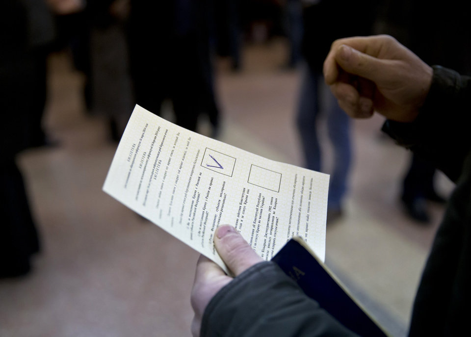 Photo - A man holds a ballot after casting a vote in favor of separation from Ukraine in the Crimean referendum in Simferopol, Ukraine, Sunday, March 16, 2014. Residents of Ukraine's Crimea region are voting in a contentious referendum on whether to split off and seek annexation by Russia. (AP Photo/Vadim Ghirda)