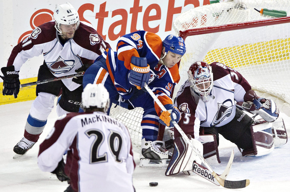 Photo - Colorado Avalanche goalie Jean-Sebastien Giguere (35) makes the save on Edmonton Oilers' Ryan Smyth (94) as Andre Benoit (61) and Nathan MacKinnon (29) chase the rebound during second period NHL hockey action in Edmonton, Alberta, on Tuesday April 8, 2014. (AP Photo/The Canadian Press, Jason Franson)