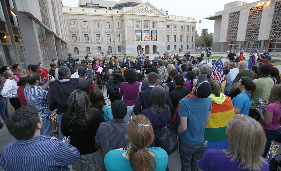 Photo - With the Arizona Capitol in the background and dozens of gay right supporters and members of the media surrounding them, Democratic representative Sen. Steve Gallardo, D-Phoenix, speaks at a podium about Arizona Gov. Jan Brewer's veto of SB1062, a bill designed to give added protection from lawsuits to people who assert their religious beliefs in refusing service to gays, at the Arizona Capitol on Wednesday, Feb. 26, 2014, in Phoenix. (AP Photo/Ross D. Franklin)