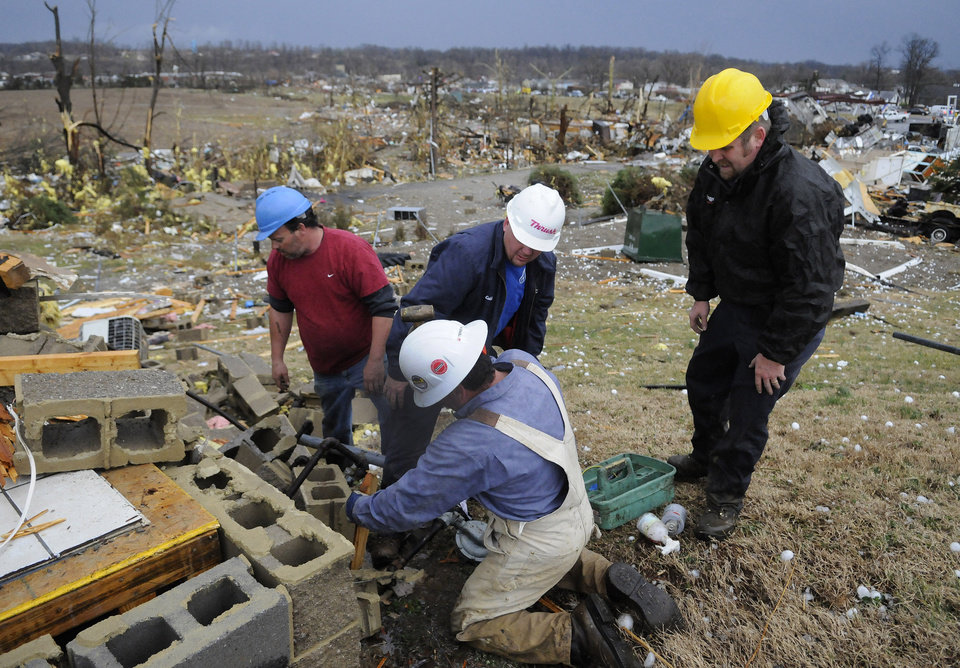 Workers with the Midwest Natural Gas Company seal a gas leak at the remains of a building following severe storms that struck Friday, March 2, 2012, in Henryville, Ind. Tornadoes ripped across several small southern Indiana towns on Friday, killing at least three people and leaving behind miles of flattened devastation along the border with Kentucky. (AP Photo/Timothy D. Easley) ORG XMIT: KYTE101