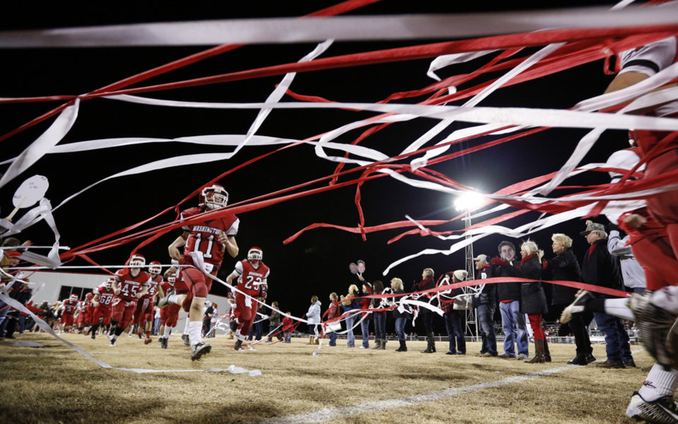 Photo - Warriors come on to the field as the Nowata Ironmen play the Washington Warriors in high school football on Friday, Nov. 28, 2014 in Washington, Okla. Photo by Steve Sisney, The Oklahoman