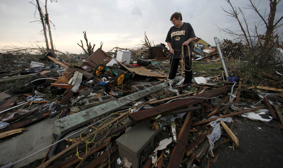 Photo - Anita Stokes salvages items from her home that was destroyed Sunday by a tornado in Joplin, Mo., Monday, May 23, 2011. A large tornado moved through much of the city Sunday, damaging a hospital and hundreds of homes and businesses and killing at least 89 people. (AP Photo/Charlie Riedel) ORG XMIT: MOCR204