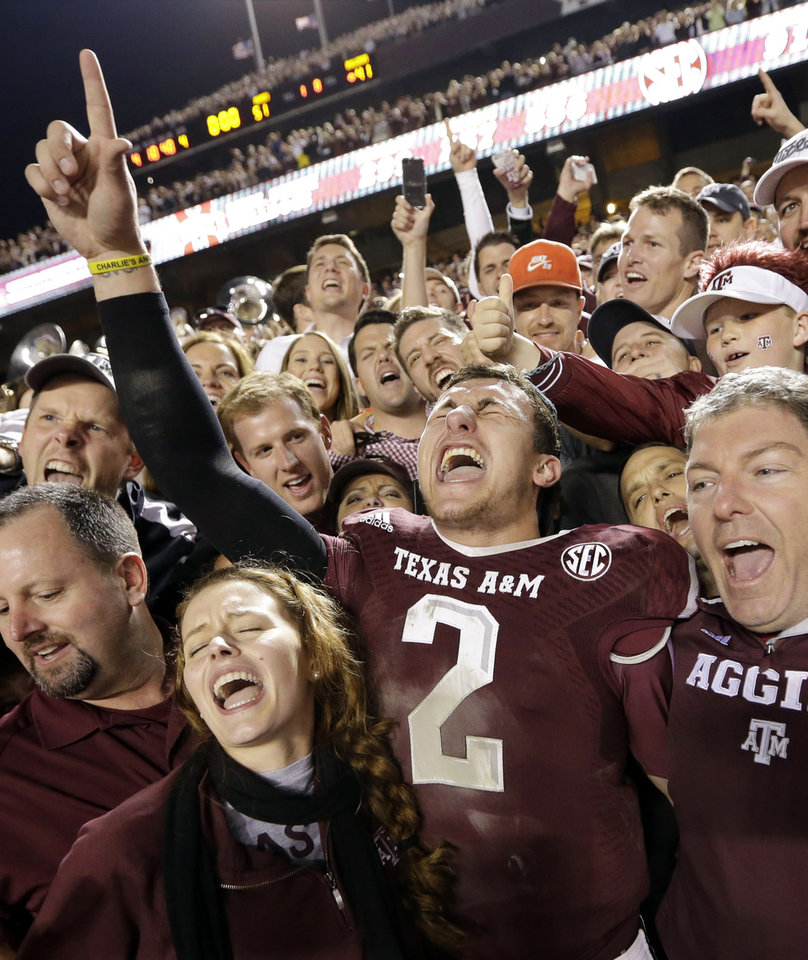 Photo - FILE - In this Nov. 9, 2013, file photo, Texas A&M quarterback Johnny Manziel (2) celebrates with fans after an NCAA college football game against Mississippi State in College Station, Texas. Manziel could be the answer to Cleveland's prayers at quarterback. The polarizing and popular Texas A&M star will likely be available when the Browns pick fourth in next week's NFL draft. (AP Photo/David J. Phillip, File)