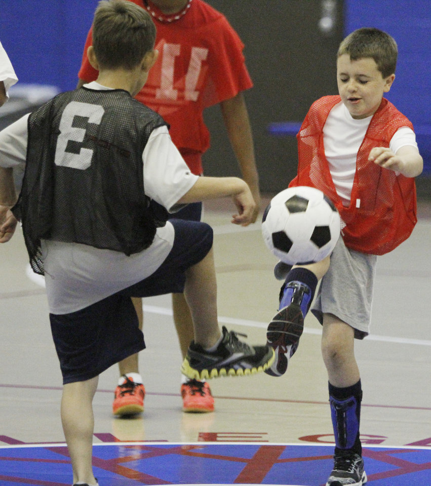 Travis Fink, 10, left, and Jacob Bichsel, 11, battle for the ball during a soccer camp scrimmage at Oklahoma City Community College in Oklahoma City, Monday 16, 2012. Photo By Steve Gooch, The Oklahoman
