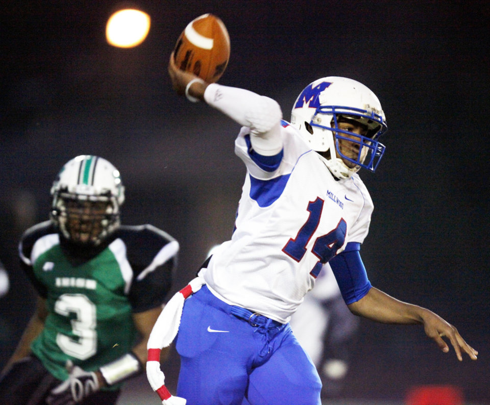 Millwood's London Potts (14) passes the ball in front of Jeffrey Pozo (3) of Bishop McGuinness during a high school football game between Millwood and Bishop McGuinness at Bishop McGuinness Catholic High School in Oklahoma City, Friday, Sept. 16, 2011. Photo by Nate Billings, The Oklahoman