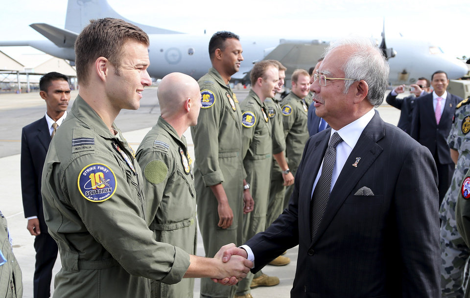 Photo - Malaysian Prime Minister Najib Razak, right, greets a Royal Australian Air Force P-3 Orion captain Lt. Russell Adams and his crew involved in the search for wreckage and debris of the missing Malaysia Airlines MH370 in Perth, Australia, Thursday, April 3, 2014.Najib was in Australia to meet with Australian Prime Minister Tonny Abbott to hold bilateral talks about the missing plane and to attend briefings with crew members. (AP Photo/Rob Griffith, Pool)