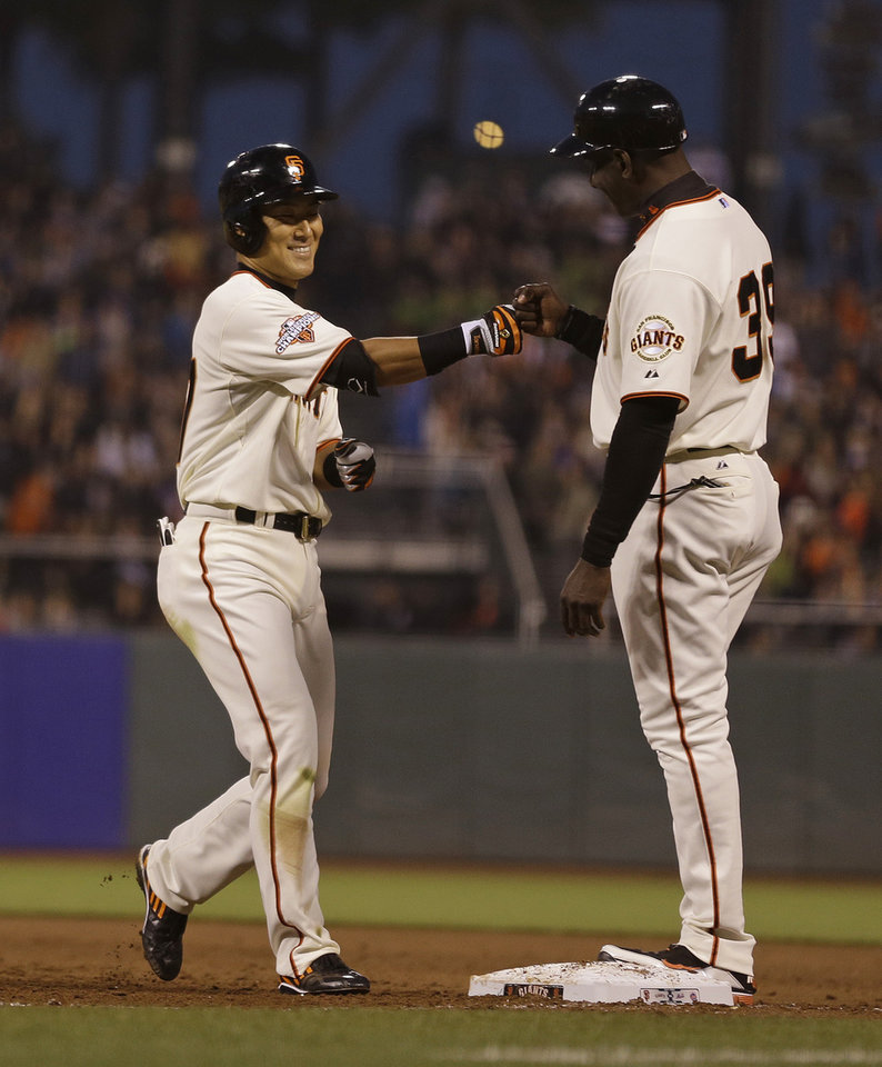 Photo - San Francisco Giants' Kensuke Tanaka, left, of Japan is greeted by first base coach Roberto Kelly, right, after getting his first Major League hit off New York Mets starting pitcher Dillon Gee in the fifth inning of their baseball game Tuesday, July 9, 2013, in San Francisco. (AP Photo/Eric Risberg)