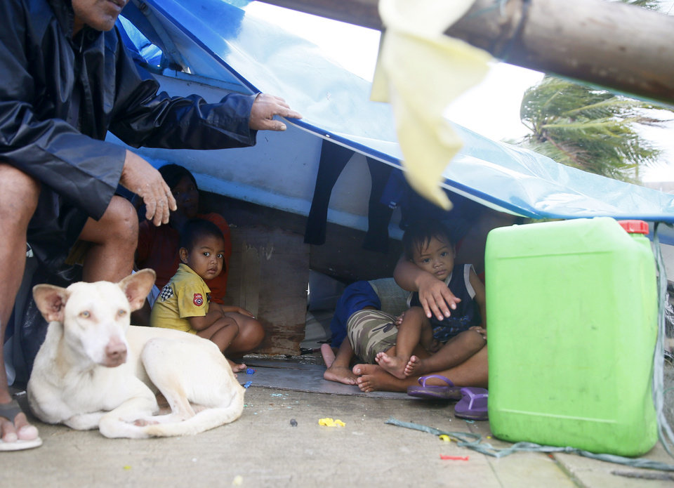 Photo - A family seeks shelter under a plastic sheet by a concrete wall amid strong wind and a slight rain brought by Typhoon Koppu Sunday, Oct. 18, 2015 in Manila, Philippines. The slow-moving typhoon blew ashore with fierce wind in the northeastern Philippines early Sunday, toppling trees and knocking out power and communications. Officials said there were no immediate reports of casualties. Thousands of villagers have been evacuated in the typhoon's path, including in towns prone to flash floods and landslides and coastal villages at risk from destructive storm surges, officials said. (AP Photo/Bullit Marquez)