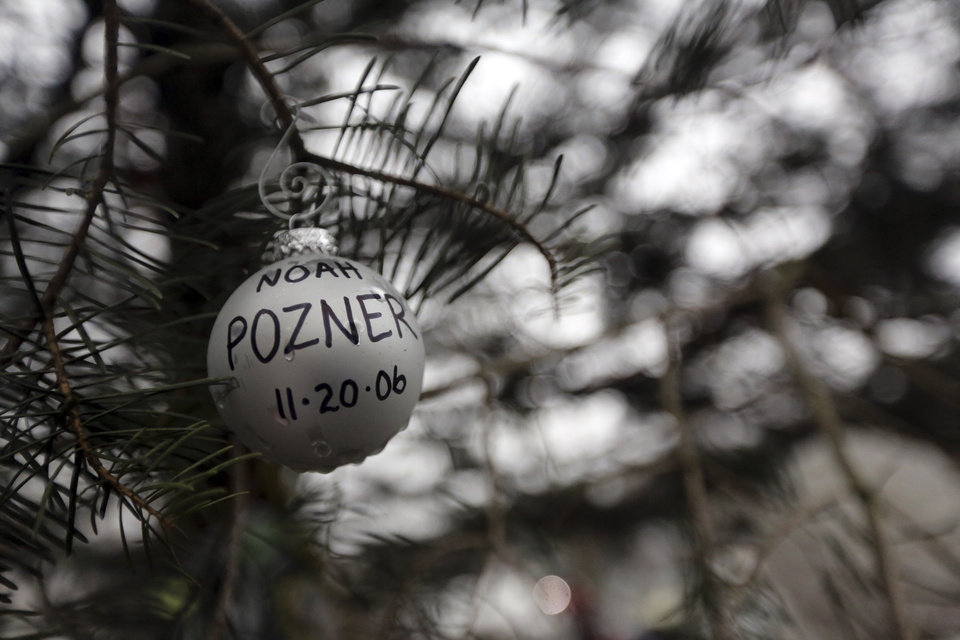 Photo - An ornament for Noah Pozner hangs on a tree at one of the makeshift memorials for the Sandy Hook Elementary School shooting, Monday, Dec. 17, 2012 in Newtown, Conn. Pozner was killed when a gunman walked into Sandy Hook Elementary School in Newtown Friday and opened fire, killing 26 people, including 20 children. (AP Photo/Mary Altaffer)