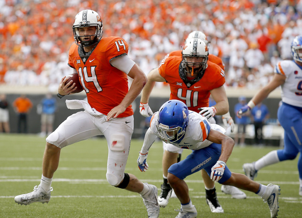 Photo - Oklahoma State's Taylor Cornelius (14) rushes as Boise State's DeAndre Pierce (4) defends during a college football game between the Oklahoma State Cowboys (OSU) and the Boise State Broncos at Boone Pickens Stadium in Stillwater, Okla., Saturday, Sept. 15, 2018. OSU won 44-21. Photo by Sarah Phipps, The Oklahoman