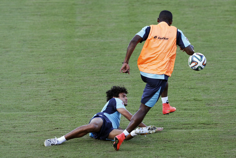 Photo - Costa Rica's Yeltsin Tejeda falls as he is tackled during a training session in Salvador, Brazil, Friday, July 4, 2014. Costa Rica play their quarterfinal match of the 2014 World Cup soccer tournament against Netherlands on July 5 in Salvador(AP Photo/Wong Maye-E)