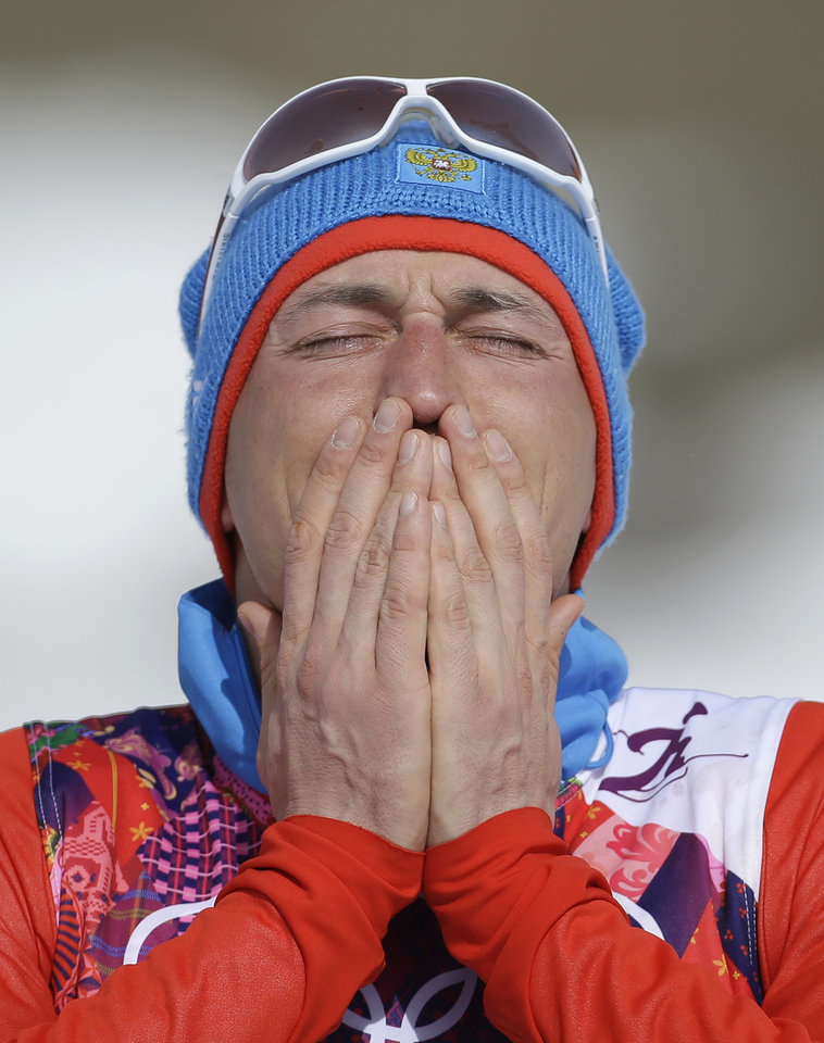 Photo - Russia's gold medal winner Alexander Legkov reacts during the flower ceremony of the men's 50K cross-country race at the 2014 Winter Olympics, Sunday, Feb. 23, 2014, in Krasnaya Polyana, Russia.  (AP Photo/Gregorio Borgia)