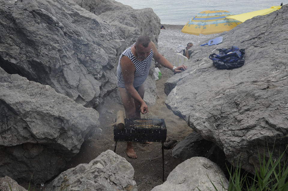 Photo - A Russian tourist cooks fish  on a Black Sea beach about 35 kms (22 miles) from Yalta, Crimea, Sunday, June 15, 2014. When Russia annexed the Black Sea peninsula of Crimea earlier this year, it regained not only harbors for its navy and abandoned Ukrainian military bases but also long stretches of pebble beaches that were the summer destination of choice for millions of Soviet citizens. The Kremlin is hoping to attract tourists to Crimea, which Russia annexed in March, by asking state-controlled companies to send their employees on free vacation trips.(AP Photo/Andrew Lubimov)