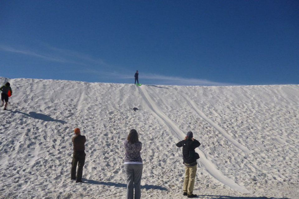 "Travel journalists get the hang of ""sledding"" on the sand at White Sands National Monument near Las Cruces, N.M. PHOTO BY KIMBERLY BURK, THE OKLAHOMAN"
