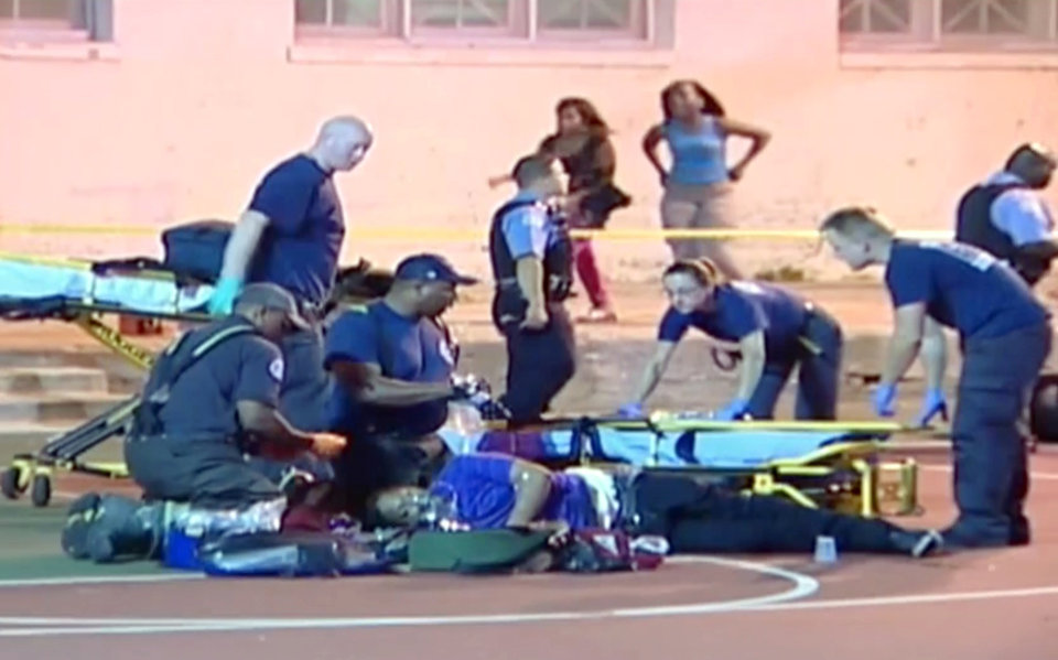 Photo - In this still frame made from Thursday, Sept. 19, 2013, video provided by Ken Herzlich, officials and emergency responders tend to a victim at the scene where a number of people, including a 3-year-old child, were shot Thursday night in a city park in Chicago. Thursday night's attack was the latest violence in a city that has struggled to stop such shootings by increasing police patrols. (AP Photo/Courtesy Ken Herzlich)