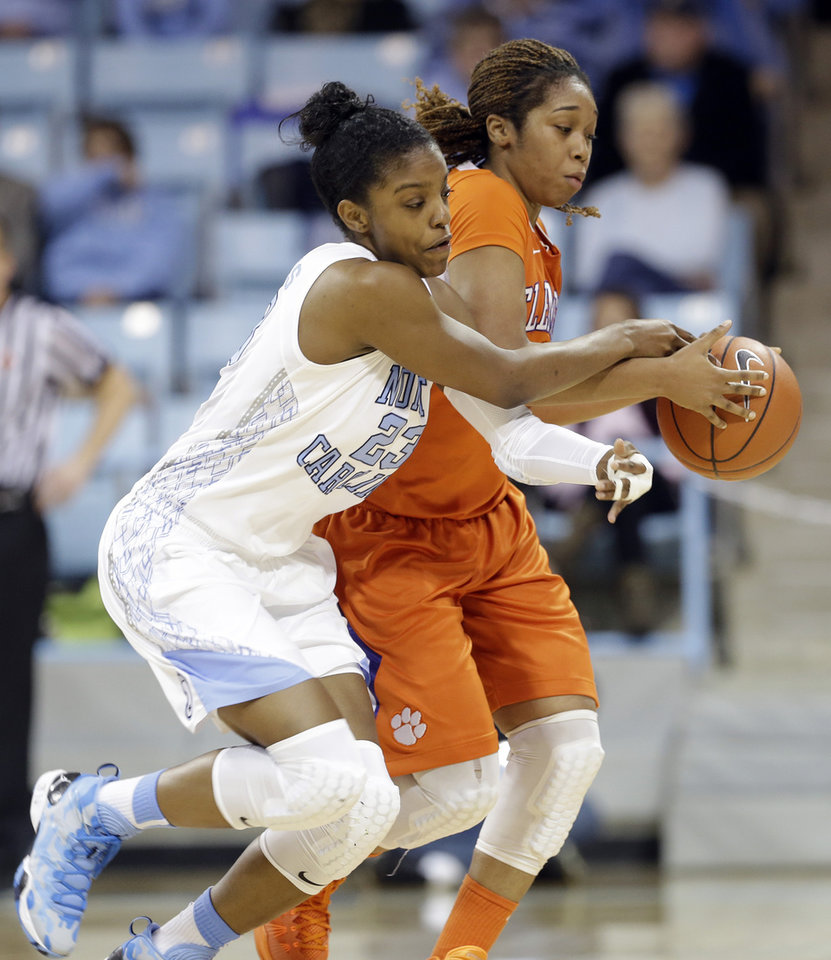 Photo - North Carolina's Diamond DeShields (23) and Clemson's Charmaine Tay chase the ball during the first half of an NCAA college basketball game in Chapel Hill, N.C., Thursday, Jan. 16, 2014. (AP Photo/Gerry Broome)