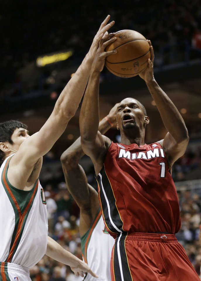 Photo - Miami Heat's Chris Bosh drives against Milwaukee Bucks' Ersan Ilyasova, left, in the first half of an NBA basketball game Friday, March 15, 2013, in Milwaukee. (AP Photo/Jeffrey Phelps)