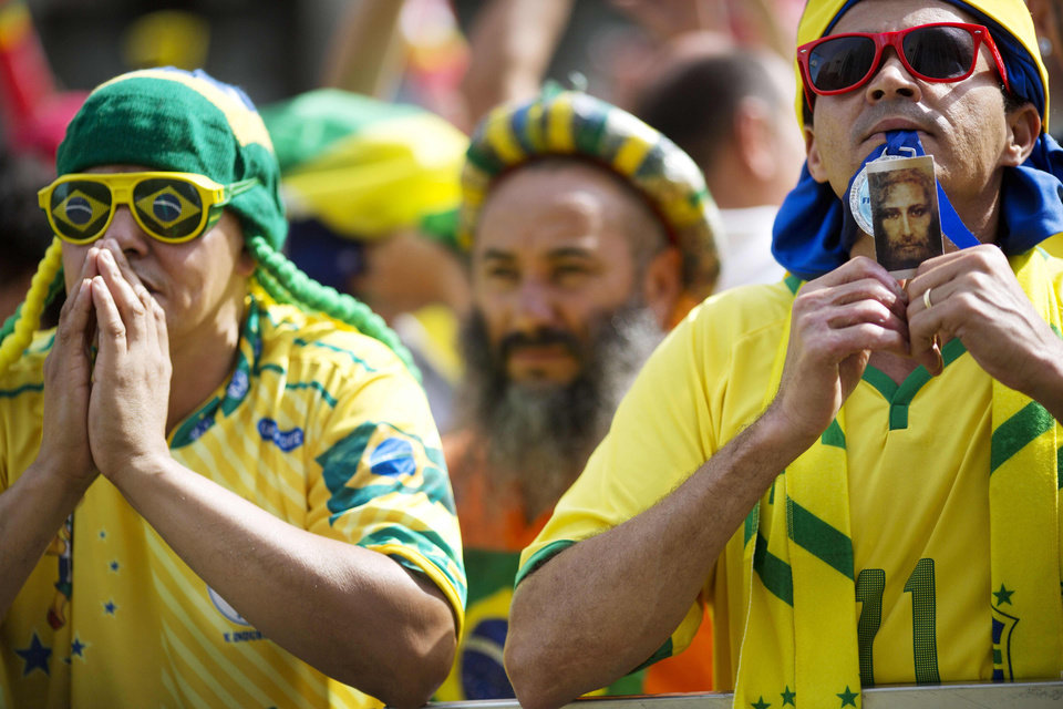 Photo - Fans of Brazil pray before a live broadcast of the World Cup round of 16 soccer match between Brazil and Chile, inside the FIFA Fan Fest area in Sao Paulo, Brazil, Saturday, June 28, 2014. (AP Photo/Rodrigo Abd)