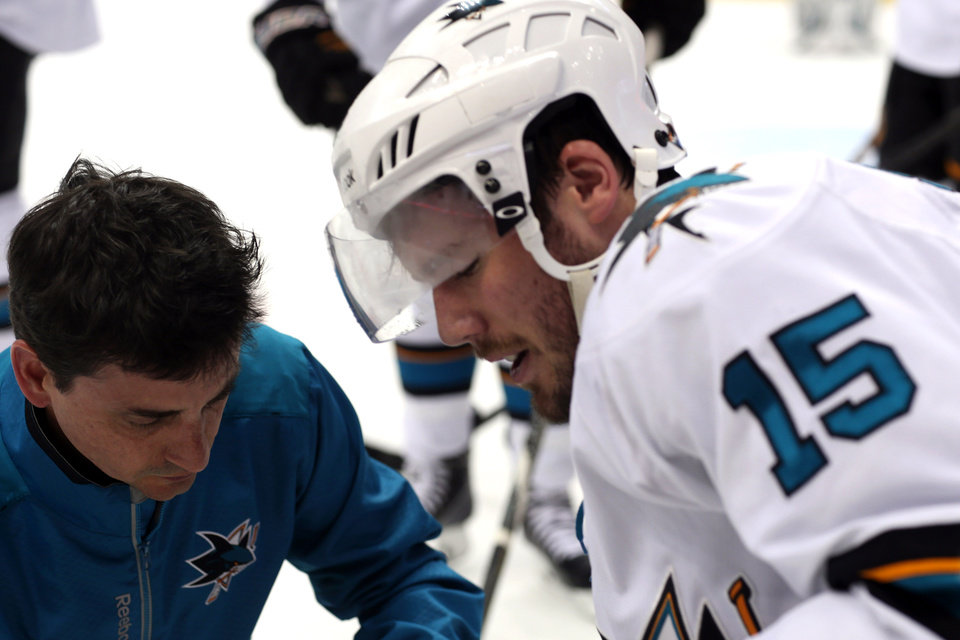 Photo - San Jose Sharks left wing James Sheppard, right, is helped off the ice after being injured while pursuing the puck with Colorado Avalanche left wing Jamie McGinn in the second period of an NHL hockey game in Denver on Saturday, March 29, 2014. (AP Photo/David Zalubowski)