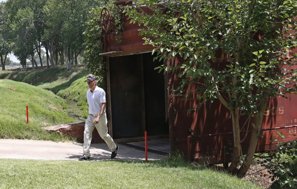 Photo - Bernhard Langer walks out of an old railroad box car that serves as a bridge during the third round of play at the 2014 U.S. Senior Open golf tournament at Oak Tree National in Edmond, Okla., Saturday, July 12, 2014. (AP Photo/Sue Ogrocki)
