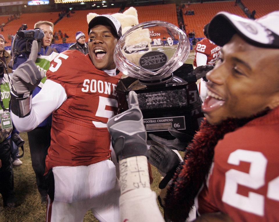 Photo - Oklahoma's Nic Harris (5) and Marcus Walker (24) celebrate with the Big 12 Championship trophy after beating Nebraska 21-7 in the the Big 12 Championship game during the University of Oklahoma Sooners (OU) college football game against the University of Nebraska Cornhuskers (NU) at Arrowhead Stadium, on Saturday, Dec. 2, 2006, in Kansas City, Mo.   by Chris Landsberger, The Oklahoman  ORG XMIT: KOD