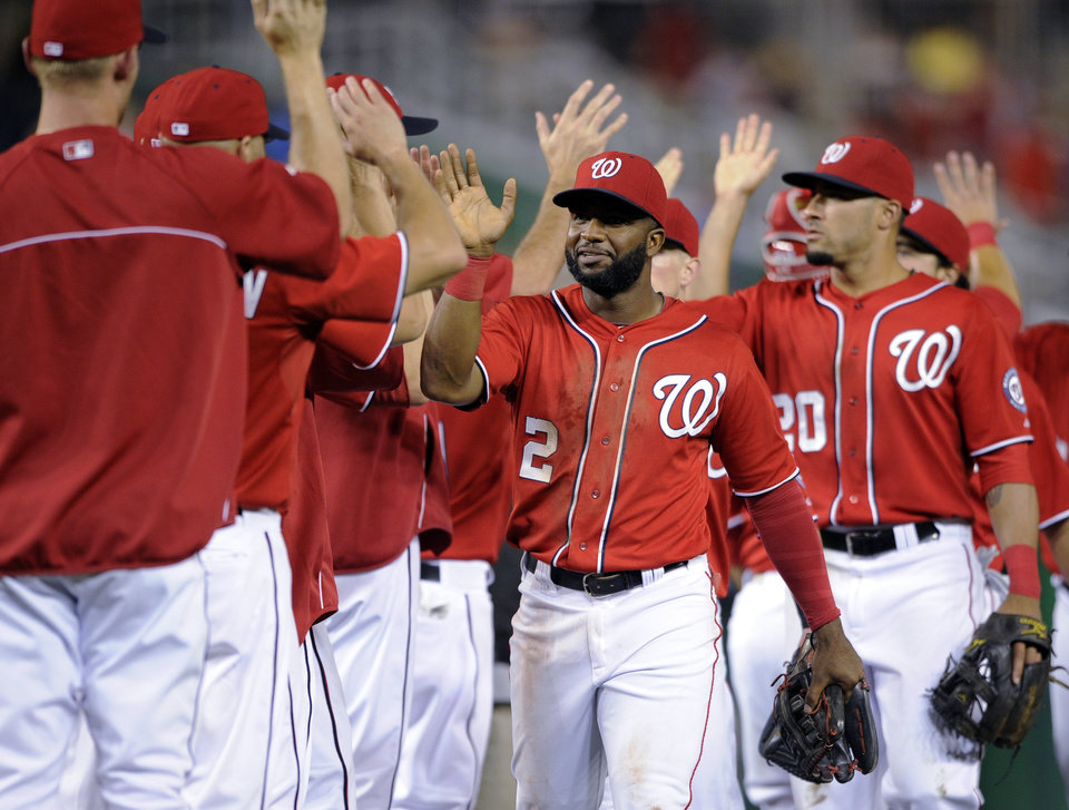 Photo - Washington Nationals' Denard Span (2), Ian Desmond (20) and others celebrate an 8-3 win over the Milwaukee Brewers in a baseball game, Saturday, July 19, 2014, in Washington. (AP Photo/Nick Wass)