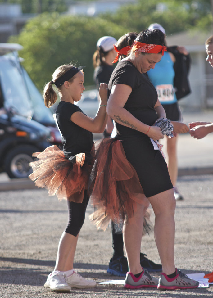 Aislym King, 10, helps pin the bib number onto Stacy Bergan before the Remember the Ten run was held in Stillwater, Okla., on April 21, 2012. Photo by Mitchell Alcala, for The Oklahoman