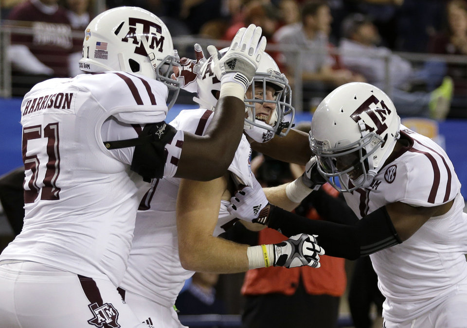 Photo - Texas A&M's Jarvis Harrison (51) and Uzoma Nwachukwu, right, celebrate with Ryan Swope, center, following his touchdown in the second half of the Cotton Bowl NCAA college football game against Oklahoma on Friday, Jan. 4, 2013, in Arlington, Texas. (AP Photo/LM Otero)