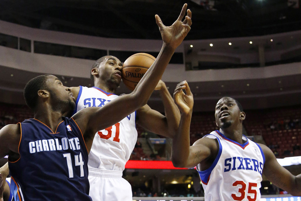 Photo - Philadelphia 76ers' Hollis Thompson (31) tries to grab a rebound with Henry Sims (35) and Charlotte Bobcats' Michael Kidd-Gilchrist (14) during the first half of an NBA basketball game, Wednesday, April 2, 2014, in Philadelphia. (AP Photo/Matt Slocum)